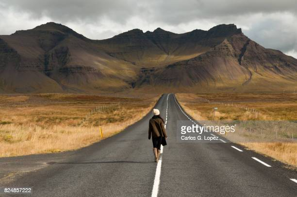 Girl walks on empty road leading to magnificent volcanic mountain