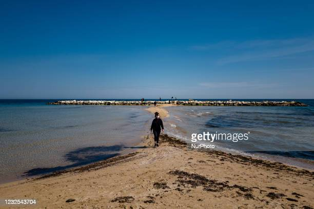 Girl walks on the beach of Pane e Pomodoro on the first day in the orange zone after more than a month in Bari on April 26, 2021. Italy tries to...