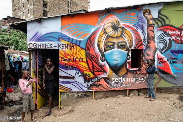 Girl walks out of a building decorated with educational graffiti about safety measures and COVID-19 on July 6, 2020 in Nairobi, Kenya. School has...