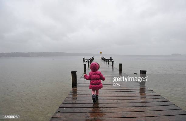 A girl walks over a bridge at the Starnberger See lake near Niederpoecking southern Germany on January 5 2013 AFP PHOTO / ANDREAS GEBERT GERMANY OUT