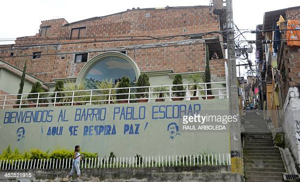 A girl walks past a wall with an inscription reading Welcome to the Pablo Escobar neighborhood Here we breathe peace at Pablo Escobar neighborhood on...