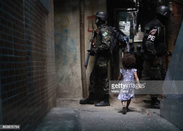 A girl walks past Brazilian soldiers standing on patrol in the Rocinha 'favela' community on September 25 2017 in Rio de Janeiro Brazil The Brazilian...