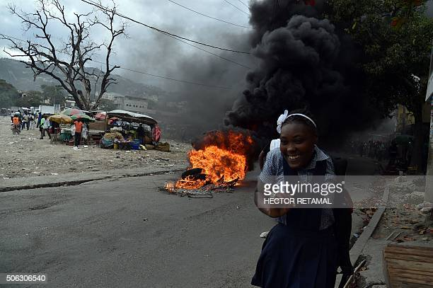 TOPSHOT A girl walks past burning tires during a protest in PortauPrince on January 22 2016 Demonstrators marched to protest against the presidential...