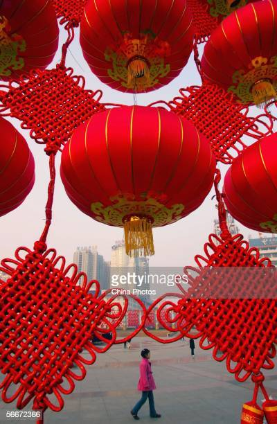 A girl walks past Chinese traditional red lanterns and Chinese knots hung to mark the upcoming Chinese new year at a street on January 26 2006 in...