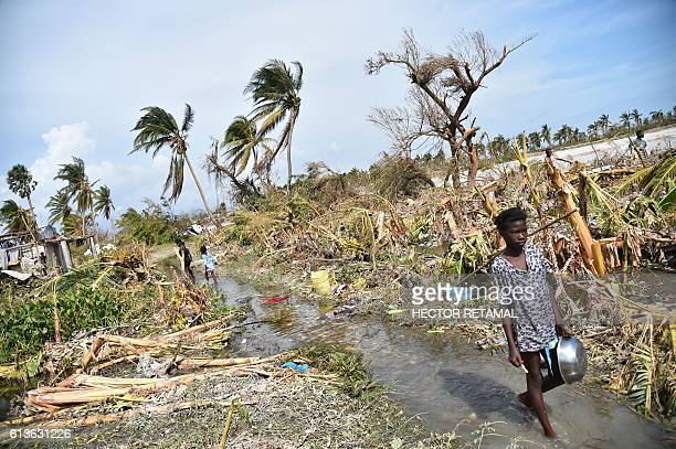 TOPSHOT A girl walks past debris left by Hurricane Matthew in Sous Roche Les Cayes in the southwest of Haiti on October 9 2016 Haiti began three days...