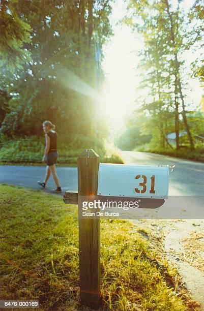 Girl Walks Past Mailbox