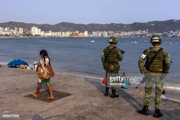 Girl walks past military police standing guard on a beach in Acapulco, Guerrero state, Mexico, on Wednesday, April 25, 2018. Through the first...