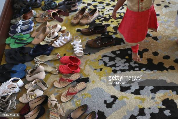 A girl walks past shoes taken off before a prayer service celebrating the Islamic holiday of EidalFitr on June 25 2017 in Stamford Connecticut The...