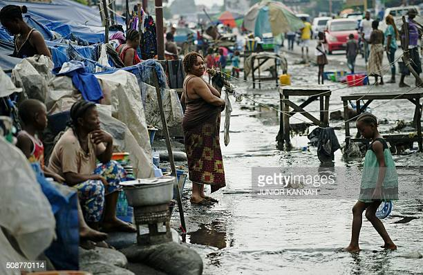 Girl walks through a flooded road to reach her makeshift home in Kinshasa on February 5, 2016. For the last seven months 167 DR Congo families have...