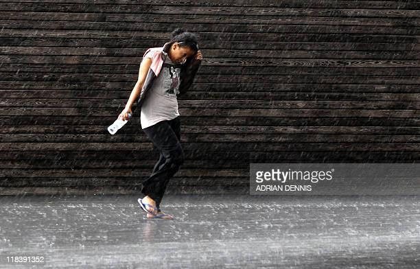 A girl walks through the rain in London on July 7 2011 AFP PHOTO ADRIAN DENNIS