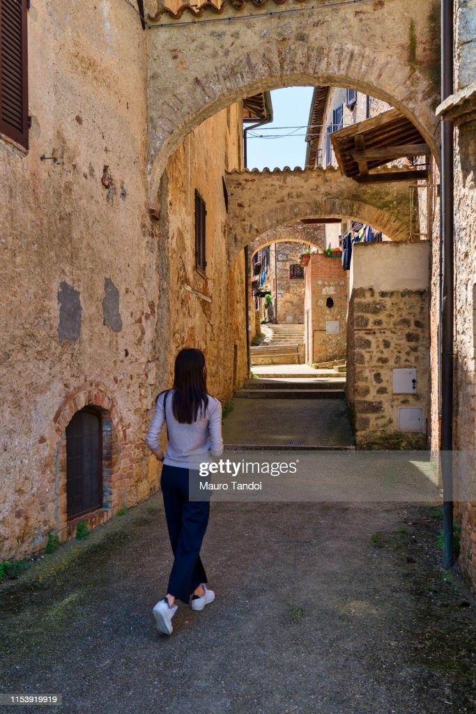 A girl walks through the streets of Abbadia Isola, Tuscany, Italy : Foto stock