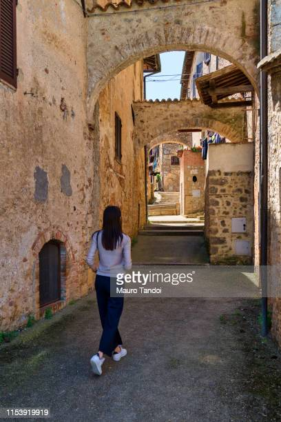 a girl walks through the streets of abbadia isola, tuscany, italy - mauro tandoi stock pictures, royalty-free photos & images