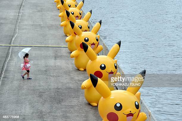 A girl walks toward a dozens of Pikachu balloons placed along side of a river in Yokohama suburban Tokyo on August 13 2015 The Pikachu mascots walk...