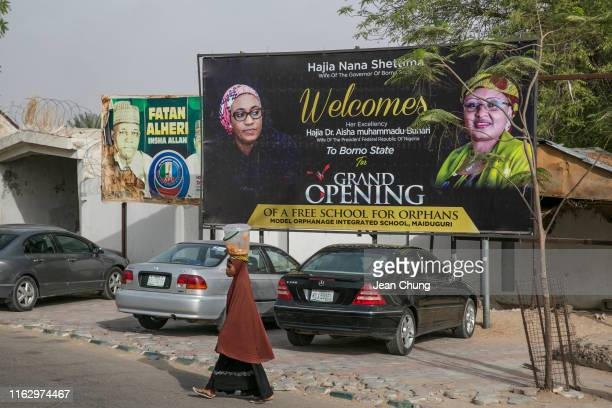 A girl walks under the political billboards that bear the portraits of Aisha Buhari at right the first lady of the Nigerian president Muhammadu...