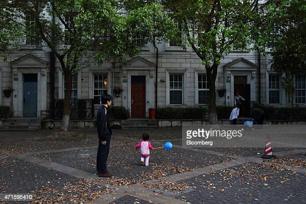 A girl walks with a ballon as a man looks on in Thames Town in Songjiang China on Sunday April 25 2015 The Englishstyle village is located about 30...