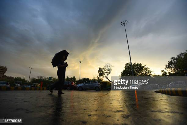 A girl walks with an umbrella during sudden rain at Mandi House on April 17 2019 in New Delhi India Strong winds accompanied by light rain lashed the...