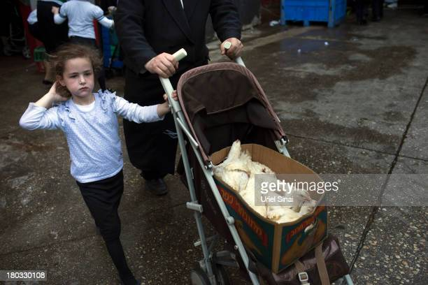 A girl walks with her father carrying chickens in a baby carriage as UltraOrthodox Jews perform the Kaparot ceremony on September 11 2013 in Bnei...