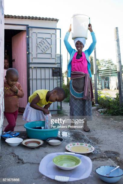 A girl washes dishes with her grandmother outside their family home on December 12 In the Barcelona section of Guguletu a township outside Cape Town...