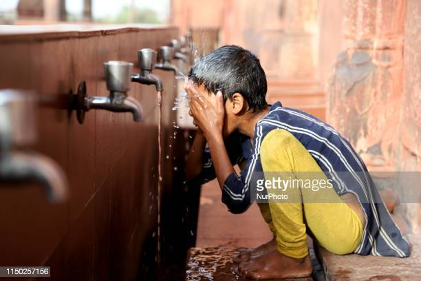 Girl washes her face on a hot summer day in New Delhi , on June 16, 2019.