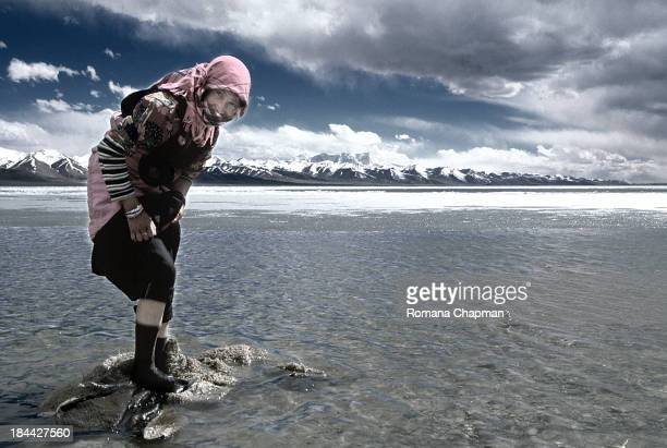 Girl washing coat in freezing cold lake. This is the way it is done without western comforts like a washing machine. It takes ages to dry the coat...