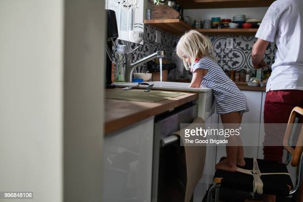 girl washing dishes at kitchen sink while father cooks breakfast - unabhängigkeit stock-fotos und bilder