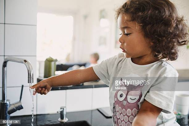 Girl washing hand under faucet in kitchen