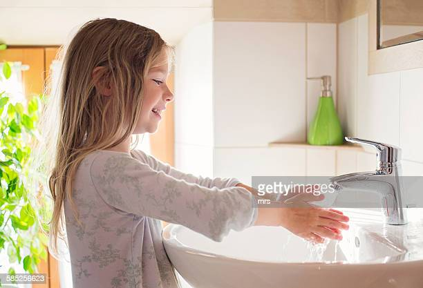 Girl washing hands in the morning