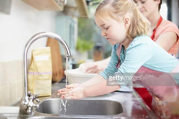 Girl washing her hands in kitchen