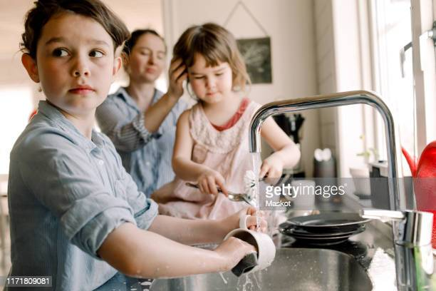 girl washing mug at kitchen sink with sister and mother in background at home - gezin met twee kinderen stockfoto's en -beelden