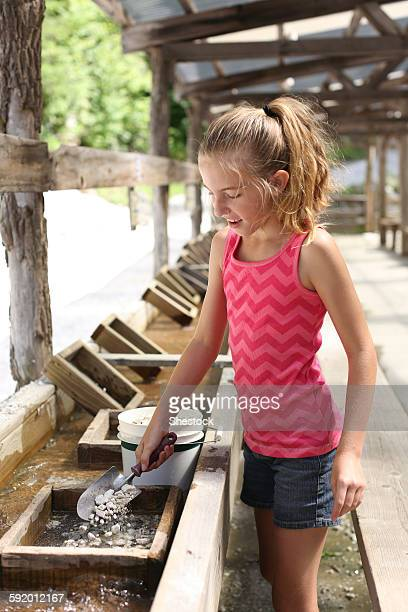 girl washing rocks in trough - trough stock photos and pictures