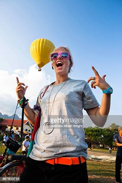 A girl watches a hot air balloon take off.