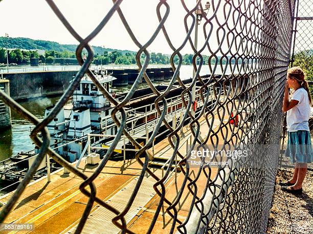 A girl watches a tug boat at a locks along the Ohio river in Pittsburgh PA. during the spring
