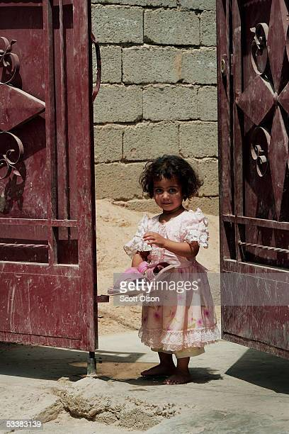 A girl watches as a patrol of US Marines from Echo Company 2nd Battalion 7th Marines passes her home while on patrol August 13 2005 in Fallujah Iraq...