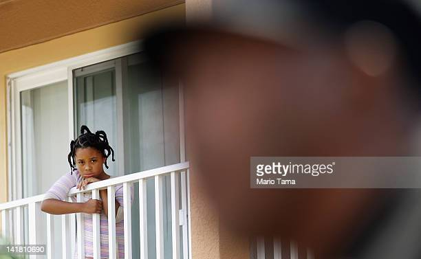 Girl watches from a balcony inside The Retreat at Twin Lakes community, where Trayvon Martin was shot and killed by George Michael Zimmerman while on...