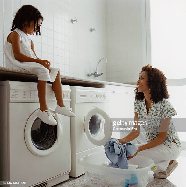 girl watches mum doing laundry - tumble dryer stock pictures, royalty-free photos & images