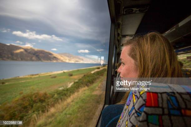 a girl watches out the bus window as the scenery passes by in new zealand. - matthew hale stock pictures, royalty-free photos & images