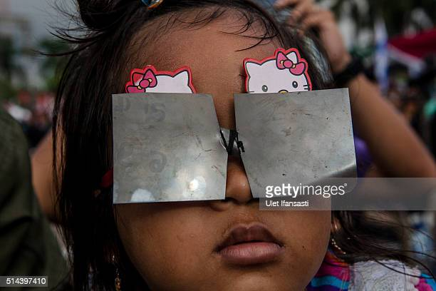 A girl watches the total solar eclipse in Palembang city on March 9 2016 in Palembang South Sumatra province Indonesia A total solar eclipse swept...