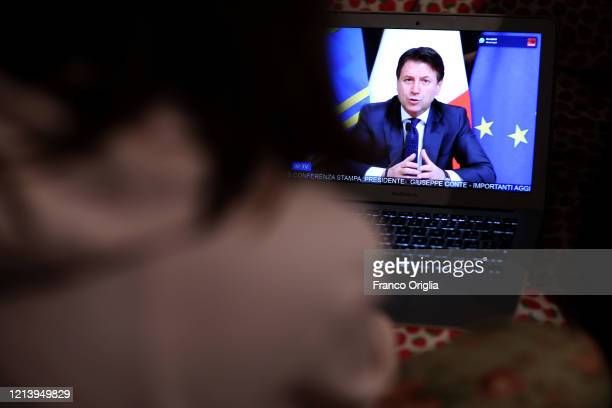 A girl watches tv as Italian Prime Minister Giuseppe Conte announces the shut down of all nonessential production activities during a special...