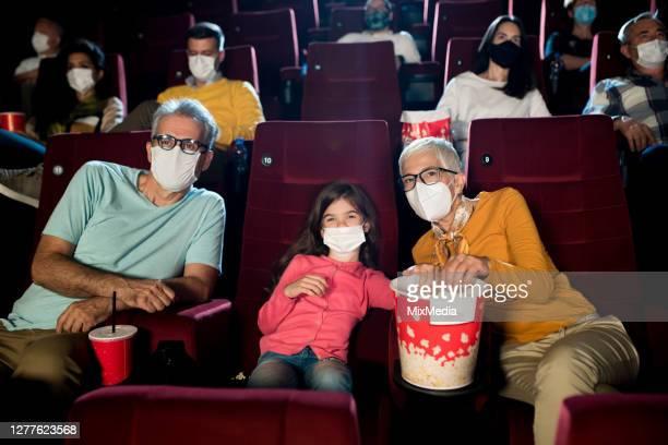 meisje dat een film bij de bioskoop met opa en oma tijdens pandemie covid-19 let - filmpremière stockfoto's en -beelden