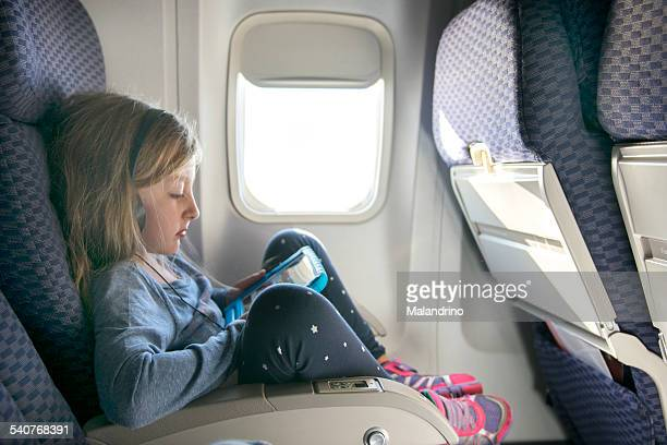 Girl watching a movie on a tablet in an airplane