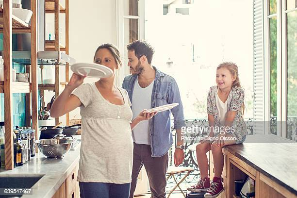 Girl watching as parents prepare family meal