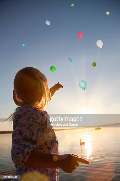 girl watching balloons floating away - releasing stock photos and pictures