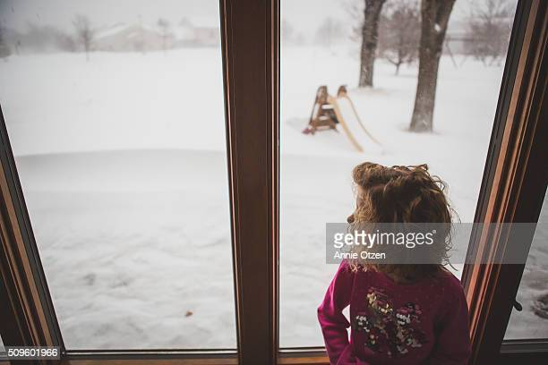 Girl watching blizzard through the window