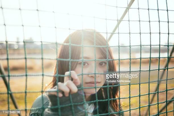 girl watching camera on river bank - yusuke nishizawa stock pictures, royalty-free photos & images