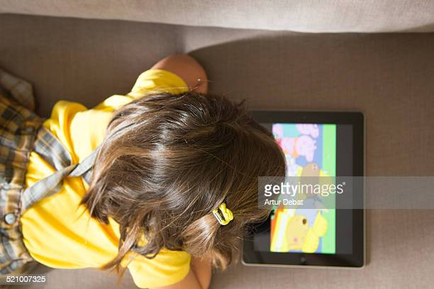 Girl watching cartoons online with the iPad tablet laying in the sofa at home with view from above