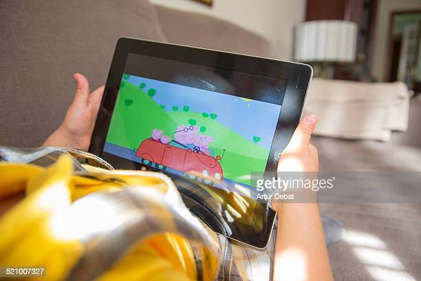 Girl watching cartoons online with the iPad tablet laying in the sofa at home