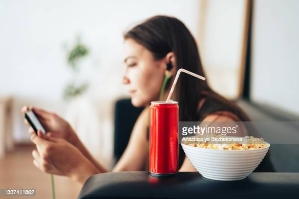 girl watching esports championship with can of juice and popcorn - international match stock pictures, royalty-free photos & images