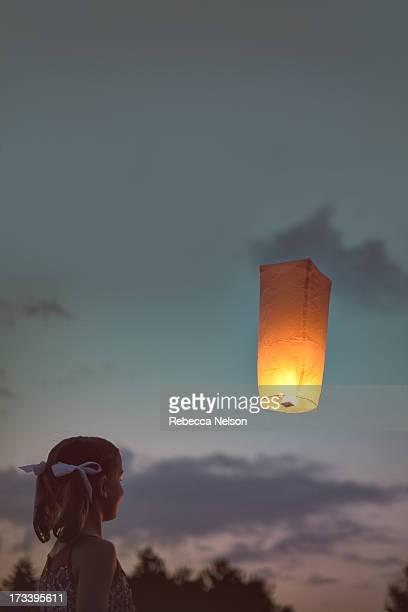 Girl watching floating sky lantern