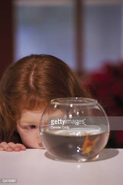 Girl (5-7) watching goldfish in glass bowl