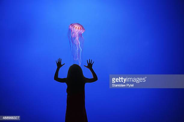 Girl watching jellyfish in aquarium